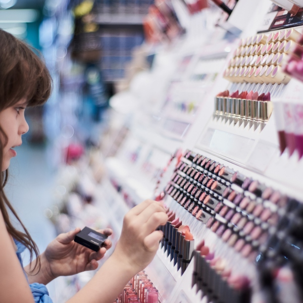 Young girl looking at make-up display (Getty Images)