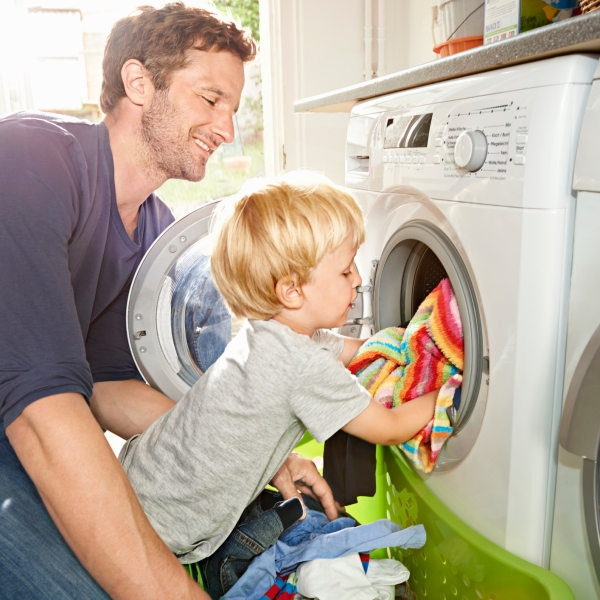 Father and son loading washing machine (Getty Images)