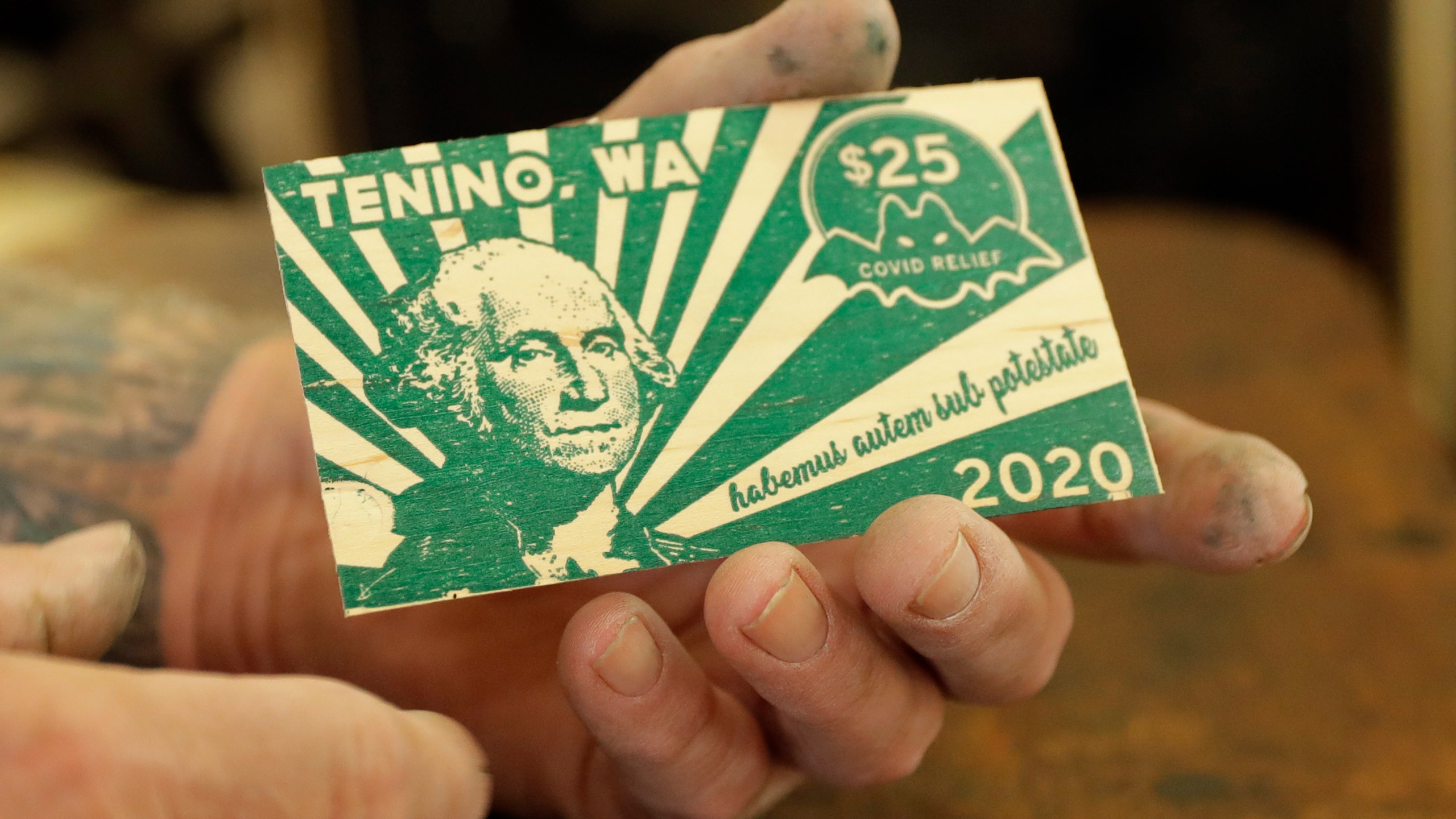 In this May 21, 2020, Loren Ackerman holds a piece of wooden money he printed on an 1890s-era press in Tenino, Wash. In an effort to help residents and local merchants alike get through the economic fallout of the coronavirus pandemic, the small town has issued wooden currency for residents to spend at local businesses, decades after it created a similar program during the Great Depression. (AP Photo/Ted S. Warren)