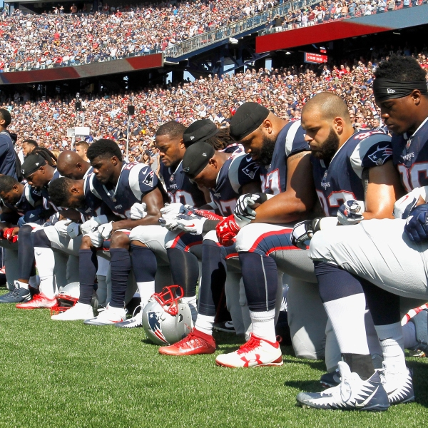 Members of the New England Patriots kneel during the National Anthem before a game. The NFL announced on Thursday it would pledge $250 million over the next ten years to help fight systematic racism. Credit: Jim Rogash/Getty Images