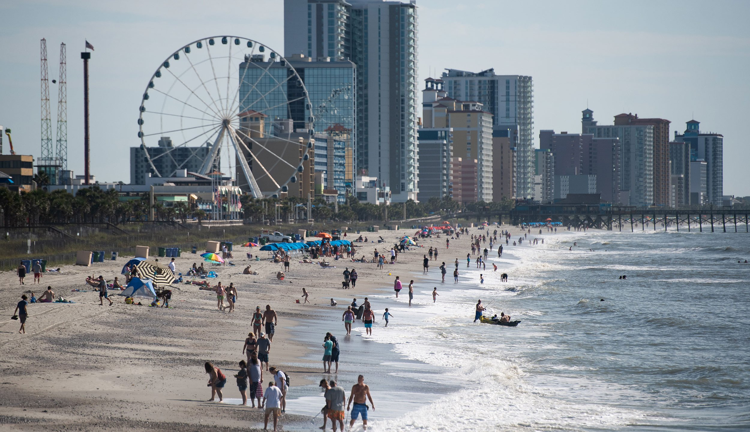 People walk and gather along the beach on the morning of May 23, 2020, in Myrtle Beach, South Carolina. (Photo by Sean Rayford/Getty Images)