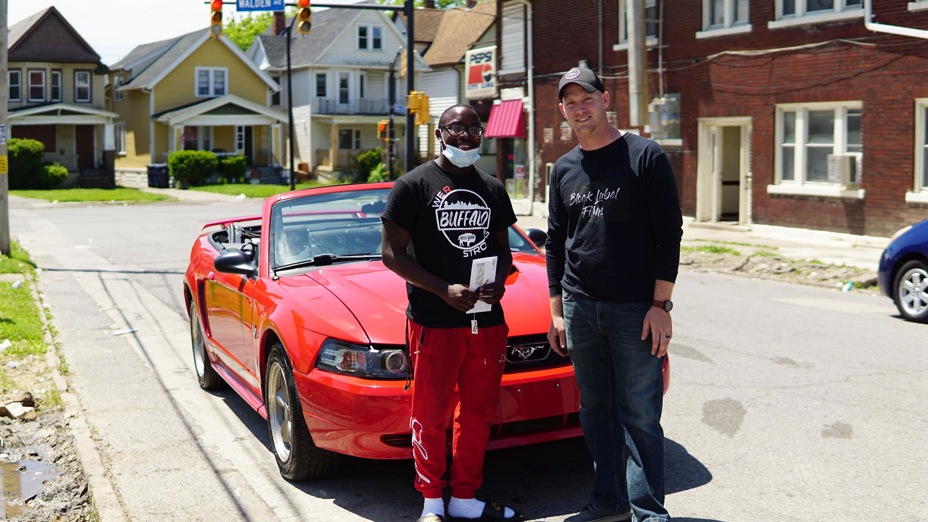 black man and white man standing in front of a red Mustang convertible with its top down