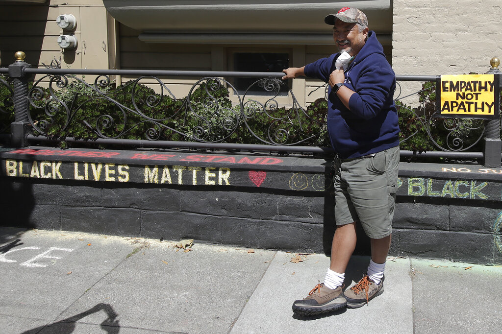 "James Juanillo stands next to chalk written outside of his home in San Francisco. The CEO of a cosmetic company issued an apology Sunday after she and her husband confronted Juanillo and threatened to call police because he stenciled ""Black Lives Matter"" in chalk on his own property, as the couple asserted that they know Juanillo doesn't live there and is therefore breaking the law. (AP Photo/Jeff Chiu)"