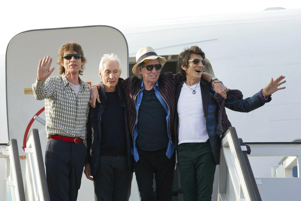 Members of The Rolling Stones, from left, Mick Jagger, Charlie Watts, Keith Richards and Ron Wood pose for photos from their plane at Jose Marti international airport in Havana, Cuba. The Rolling Stones are threatening U.S. President Donald Trump with legal action for using their songs at his reelection campaign rallies despite cease-and-desist directives, according to a statement issued by the band Sunday. (AP Photo/Ramon Espinosa File)