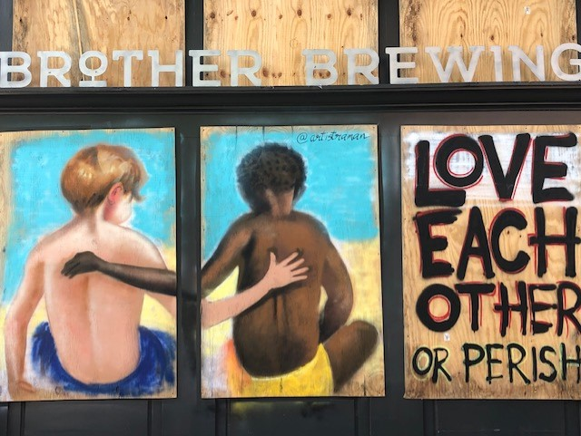 Art has begun to appear on the boarded-up storefront windows in downtown Greensboro.