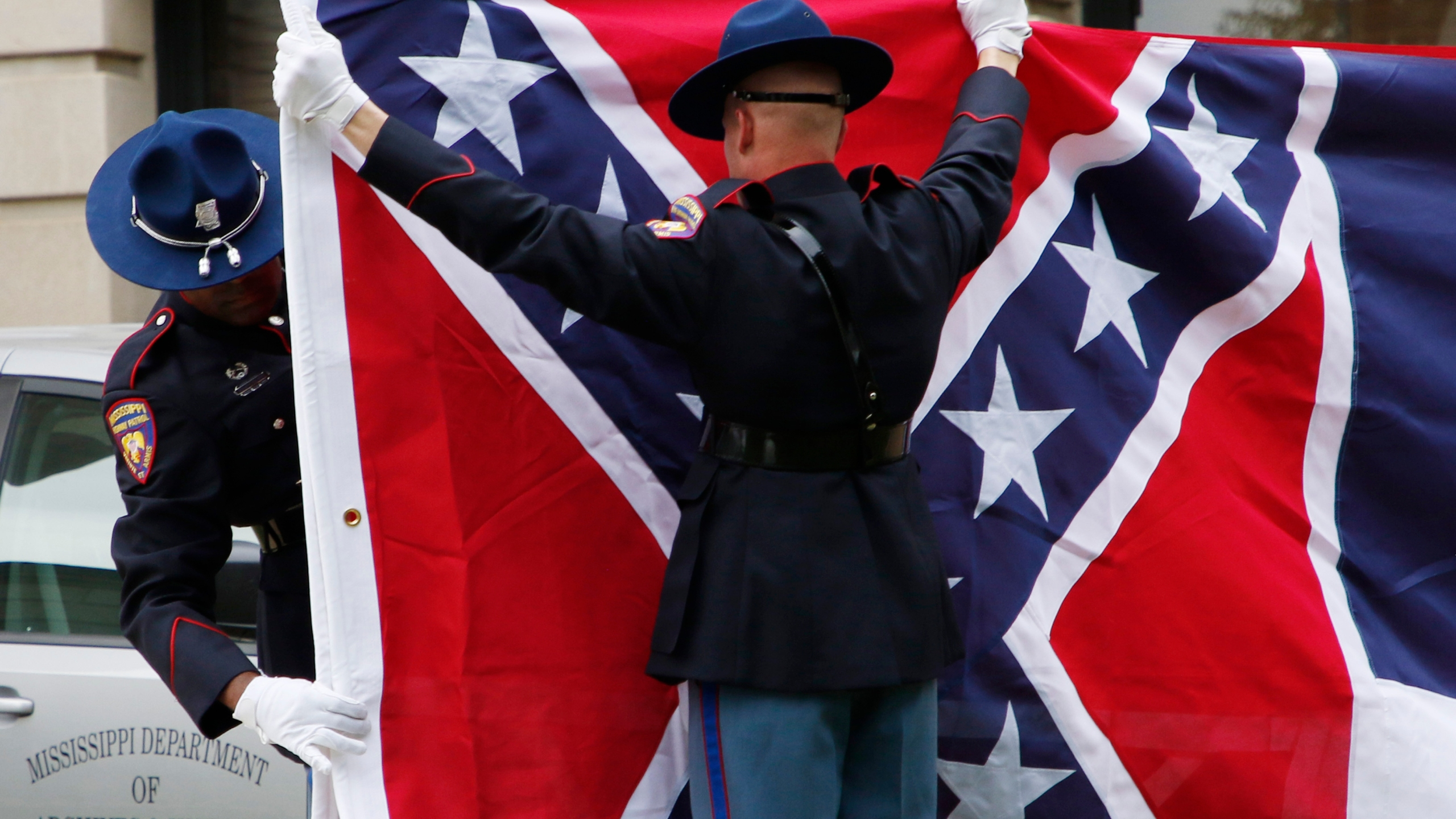 A Mississippi Highway Safety Patrol honor guard folds the retired Mississippi state flag after it was raised over the Capitol grounds one final time in Jackson, Miss., on July 1, 2020. Vestiges of the Civil War and Jim Crow segregation are coming down across the Old Confederacy as part of a national reckoning on race and white supremacy. A diversifying Democratic Party hopes the changes in symbols are part of a more fundamental shift in a region that dominated by Republicans for a generation – and white conservative Democrats a century before that. (AP Photo/Rogelio V. Solis)