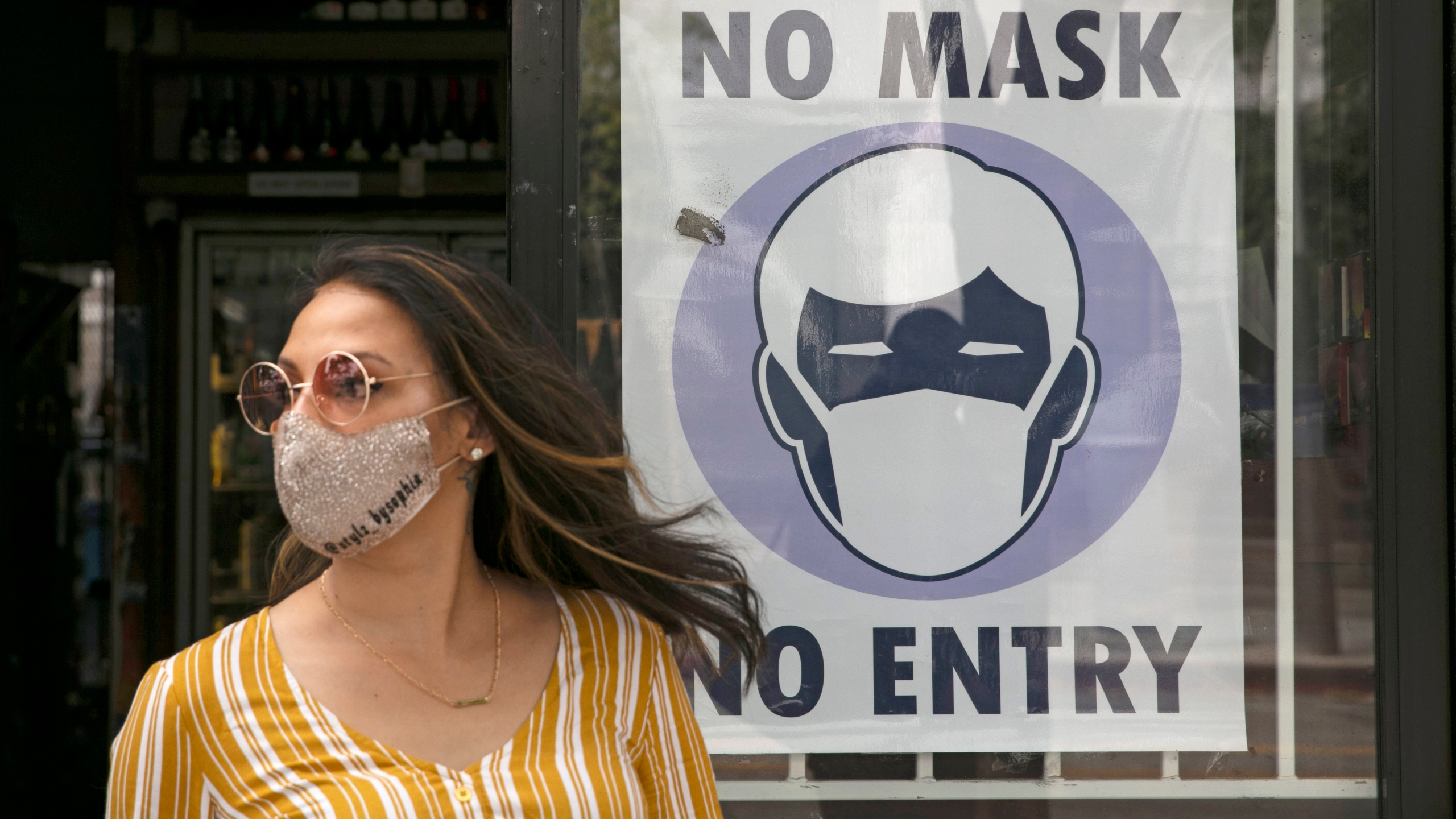 FILE - A woman walks out of a liquor store past a sign requesting its customers to wear a mask Tuesday, June 23, 2020, in Santa Monica, Calif. According to a new poll, Americans overwhelmingly are in favor of requiring people to wear masks around other people outside their homes, reflecting fresh alarm over spiking infection rates. The poll also shows increasing disapproval of the federal government's response to the pandemic. California is among the states seeing the greatest surge in cases now. (AP Photo/Jae C. Hong, File)