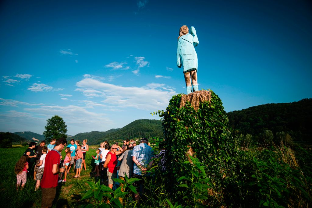 People gather around what conceptual artist Ales 'Maxi' Zupevc claims is the first ever monument of Melania Trump, set in the fields near the town of Sevnica, US First Ladys hometown, during a small inauguration celebration on July 5, 2019. - After Melania cake, Melania honey, and even Melania slippers, the Slovenian hometown of the US's first lady will now boast a statue of its most famous daughter -- albeit one which has faced decidedly mixed reviews. The life-size statue on the outskirts of Sevnica was inaugurated on July 5, 2019. (Photo by Jure Makovec / AFP) / RESTRICTED TO EDITORIAL USE - MANDATORY MENTION OF THE ARTIST UPON PUBLICATION - TO ILLUSTRATE THE EVENT AS SPECIFIED IN THE CAPTION (Photo credit should read JURE MAKOVEC/AFP via Getty Images)