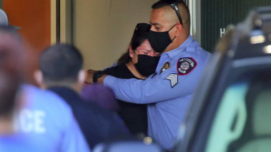 A McAllen police officer hugs a mourner at McAllen Medical Center, Saturday, July 11, 2020, in McAllen, Texas. Two police officers were shot and killed after reportedly responding to a disturbance call. (Joel Martinez/The Monitor via AP)