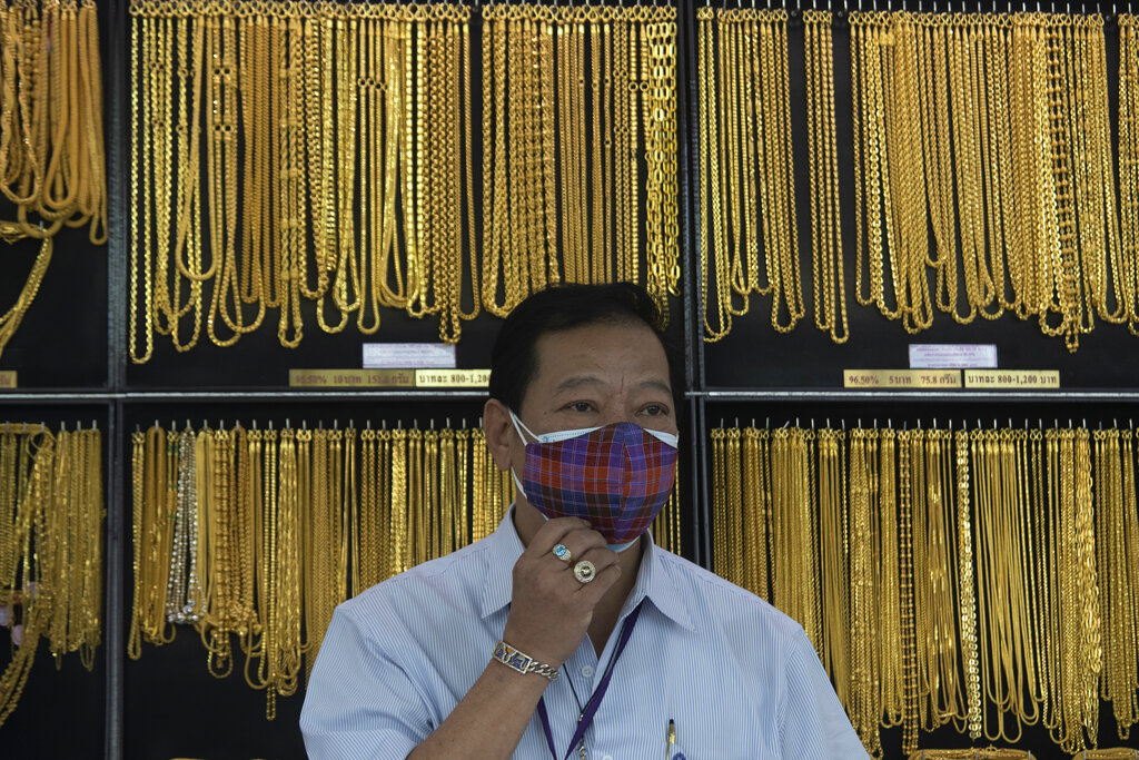 A Thai shopkeeper adjusts his face mask at a gold shop in Bangkok, Thailand. The price of gold surged more than $30 on Monday to over $1,926 per ounce as investors step up buying of the precious metal often sought in times of uncertainty. (AP Photo/Sakchai Lalit, File)
