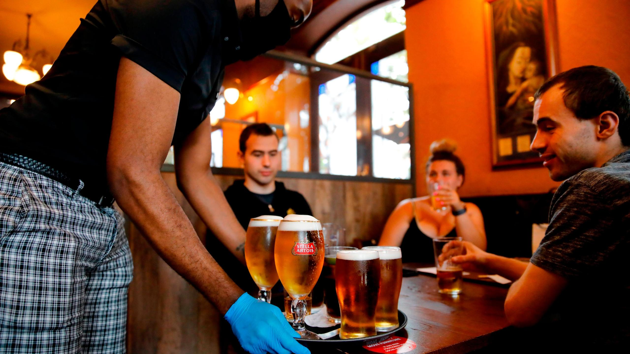 A member of bar staff wearing PPE (personal protective equipment) in the form of golves and a face mask. The World Health Organization on Thursday released a new scientific report detailing how the coronavirus can pass from one person to the next -- including through the air during certain medical procedures, and possibly through the air in crowded indoor spaces. (TOLGA AKMEN/AFP/Getty Images)