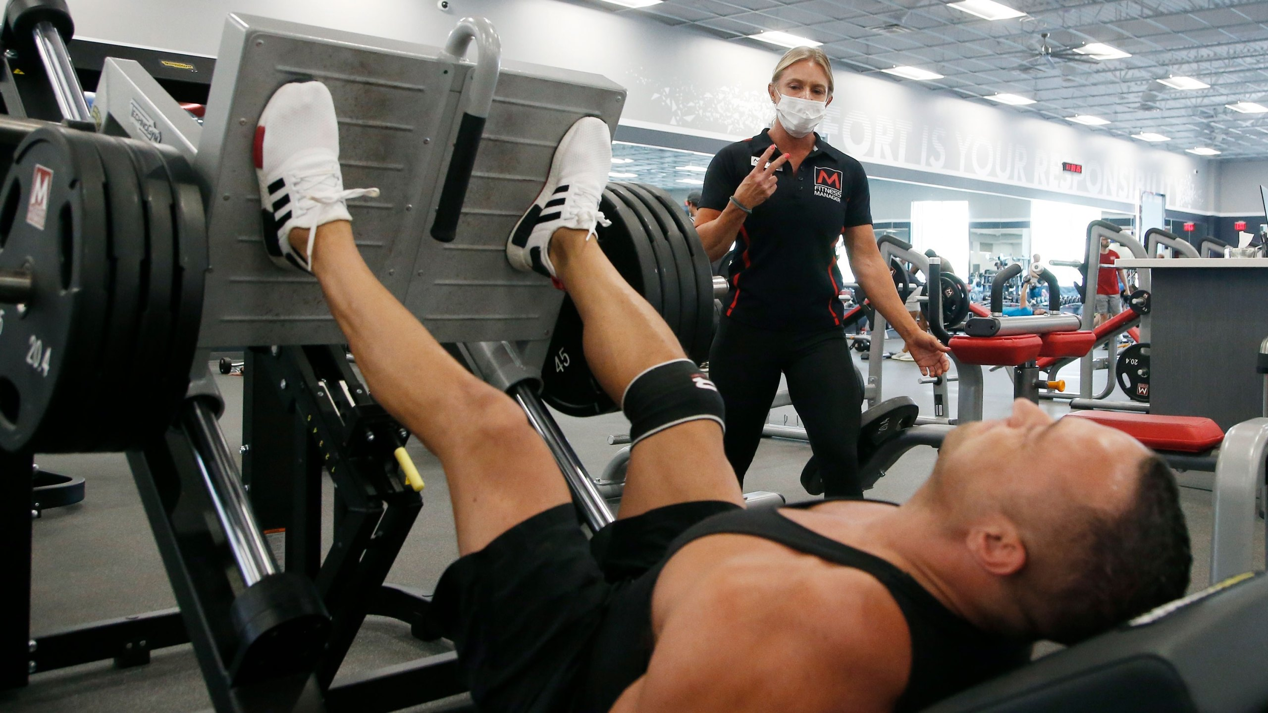 A trainer, top, at Mountainside Fitness, works with a client as the facility remains open even as Arizona Gov. Doug Ducey has issued an executive order for all gyms to close due to the surge in coronavirus cases in Arizona Thursday, July 2, 2020, in Phoenix. For the third straight day, several health clubs in metro Phoenix were defying Ducey's 30-day shutdown order to close gyms, bars, water park and tubing businesses, raising questions about whether officials who have been criticized for responding indecisively to the pandemic will be effective in shutting down the clubs. (AP Photo/Ross D. Franklin)