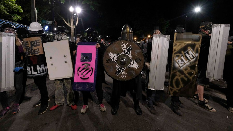 Protesters holding shields line up in the street opposite the Edith Green Wendell Wyatt federal building as demonstrations against police brutality outside the federal courthouse and Justice Center in downtown Portland, Ore., on July 18, 2020. (Photo by Alex Milan Tracy/Sipa USA)(Sipa via AP Images)