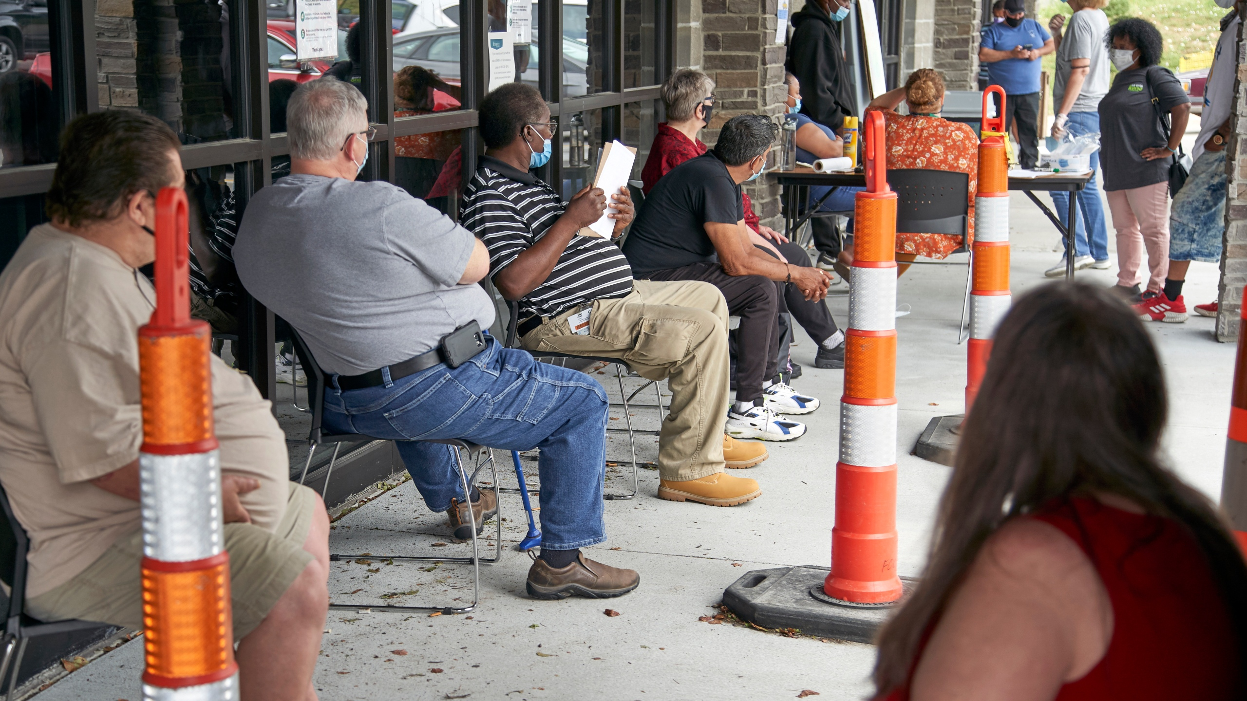 FILE - In this July 15, 2020, file photo, job seekers exercise social distancing as they wait to be called into the Heartland Workforce Solutions office in Omaha, Neb. The extra $600 in weekly unemployment benefits has expired, the federal eviction moratorium has ended and federal money to help businesses retain workers has grown lean. Meanwhile, the pandemic rages on and there is no consensus from Washington on another relief package. (AP Photo/Nati Harnik, File)