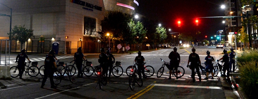 Charlotte Mecklenburg Police bike officers wait at the intersection of Brevard Street and Stonewall Street as demonstrators protest, in uptown Charlotte, N.C., Friday, Aug. 21, 2020. (Jeff Siner/The Charlotte Observer via AP)