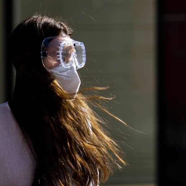 LONDON, ENGLAND - APRIL 22: A woman wearing a face mask and goggles walks near Elephant and Castle underground station on April 22, 2020 in London, England. The British government has extended the lockdown restrictions first introduced on March 23 that are meant to slow the spread of COVID-19. (Photo by Dan Kitwood/Getty Images)