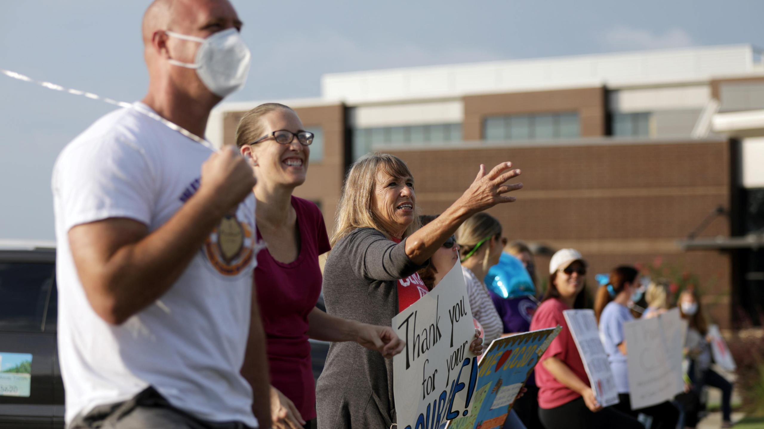 Supporters of the Cherokee County School District's decision to reopen schools cheer on faculty arriving to the district's headquarters in Canton, Georgia. Credit: Dustin Chambers/Reuters