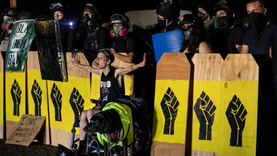 PORTLAND, OR - AUGUST 15 : A handicapped protester screams at police during a standoff at a Portland precinct in Portland, Oregon on August 15, 2020. Protests have continued for the 80th consecutive night in Portland since the killing of George Floyd. (Photo by Paula Bronstein/Getty Images )