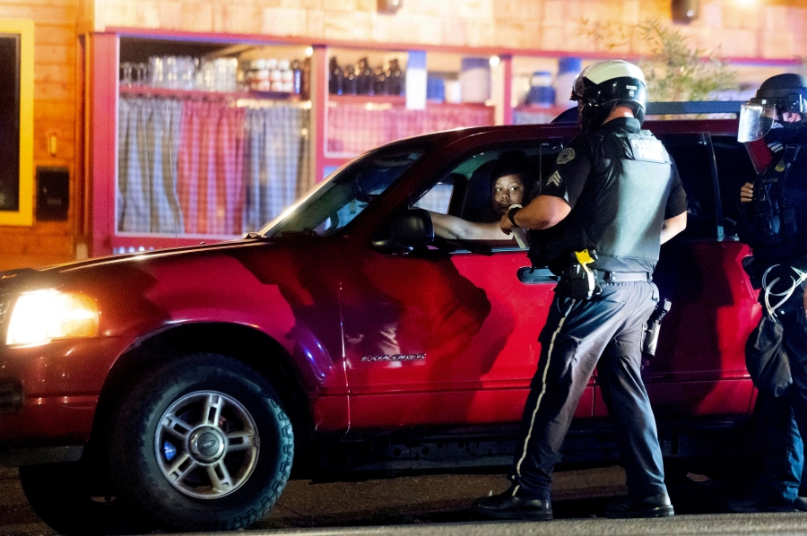 Police officers make a traffic stop near a Black Lives Matter protest on Friday, Sept. 4, 2020, in Portland, Ore. This weekend Portland will mark 100 consecutive days of protests over the May 25 police killing of George Floyd. (AP Photo/Noah Berger)