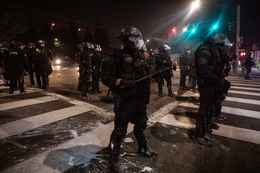 Police stand guard as protesters take to the streets Friday, Sept. 4, 2020 in Portland, Ore. This weekend Portland will mark 100 consecutive days of protests over the May 25 police killing of George Floyd. (AP Photo/Paula Bronstein)