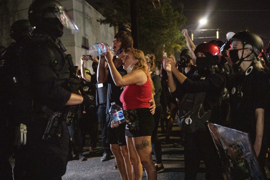 Protesters standoff with police as they take to the streets Friday, Sept. 4, 2020 in Portland, Ore. This weekend Portland will mark 100 consecutive days of protests over the May 25 police killing of George Floyd. (AP Photo/Paula Bronstein)