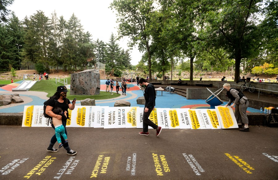 During the 100th consecutive day of demonstrations in Portland, Ore., the stenciled names of Black people who died line a pathway on Saturday, Sept. 5, 2020. The protests, which began over the killing of George Floyd, have led to two deaths and frequent clashes between protesters and law enforcement. (AP Photo/Noah Berger)