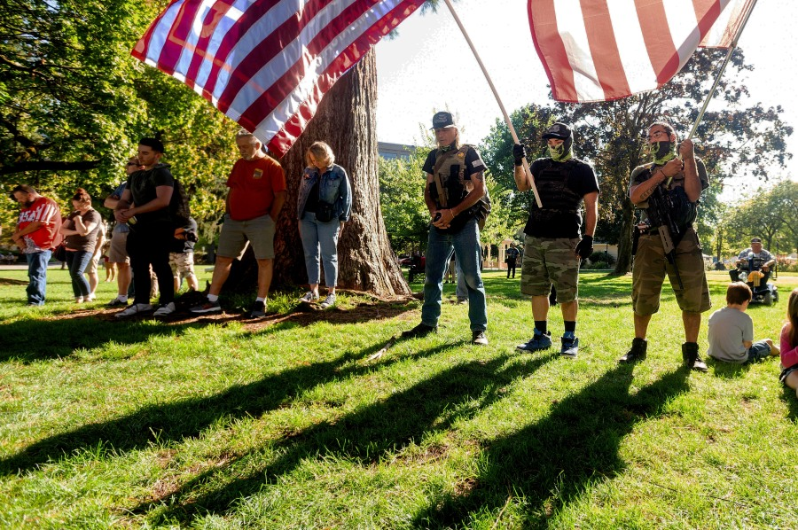Mourners, who declined to give their names, listen to a prayer during a memorial for Aaron J. Danielson on Saturday, Sept. 5, 2020, in Vancouver, Wash. Danielson, a supporter of the conservative group Patriot Prayer, was fatally shot in August as supporters of President Donald Trump and Black Lives Matter protesters clashed in Portland, Ore. (AP Photo/Noah Berger)