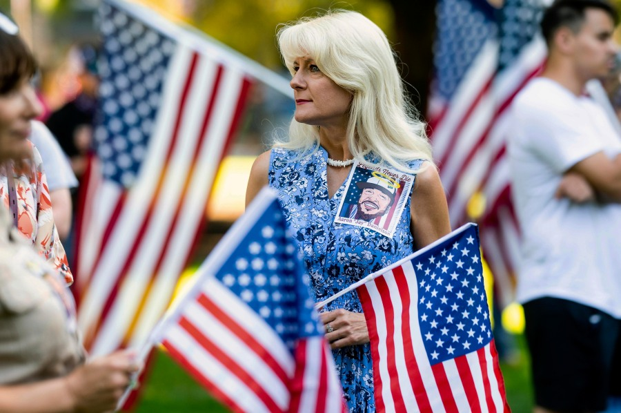 A woman wears an image of Aaron J. Danielson during a memorial for him on Saturday, Sept. 5, 2020, in Vancouver, Wash. Danielson, a supporter of the conservative group Patriot Prayer, was fatally shot in August as supporters of President Donald Trump and Black Lives Matter protesters clashed in Portland, Ore. (AP Photo/Noah Berger)