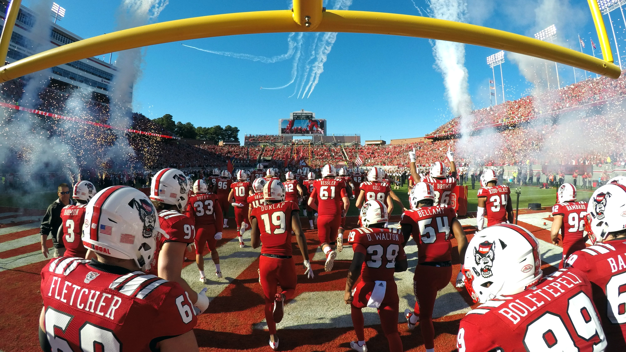 RALEIGH, NC - NOVEMBER 03: Players of the North Carolina State Wolfpack run onto the field as planes fly overhead prior to their game against the Florida State Seminoles at Carter-Finley Stadium on November 3, 2018 in Raleigh, North Carolina. (Photo by Lance King/Getty Images)