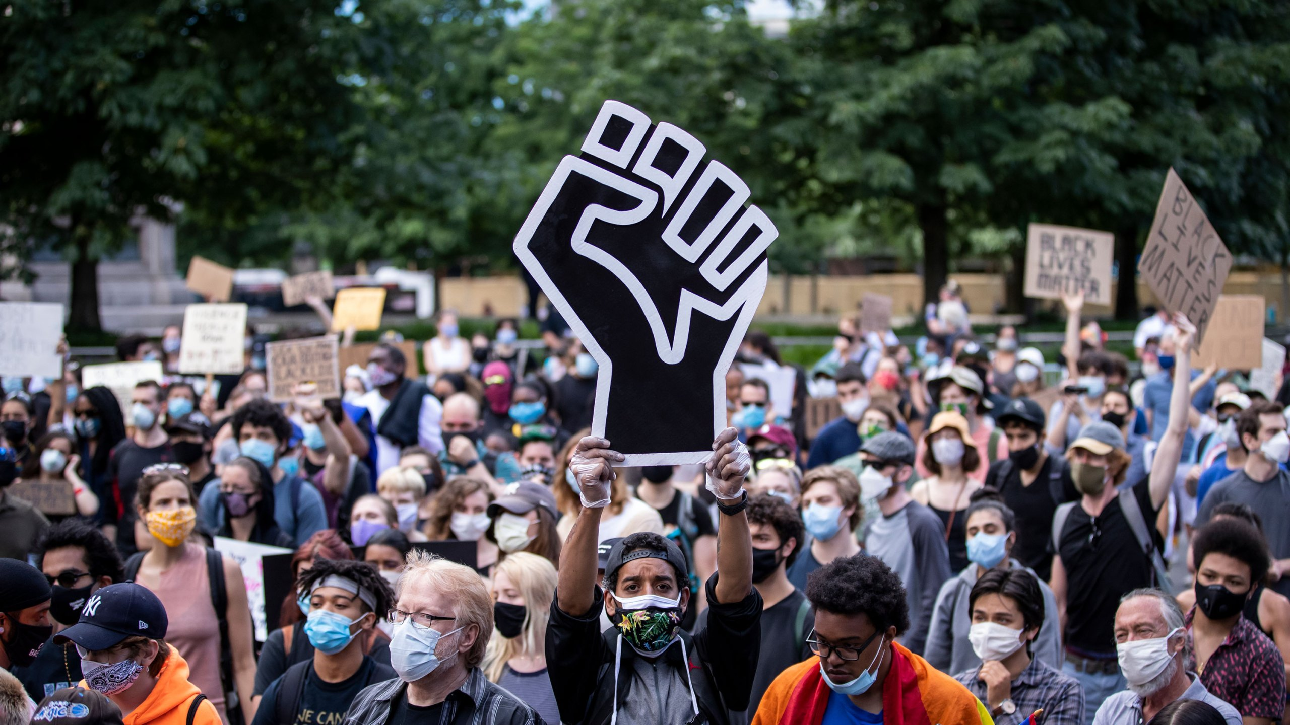"""MANHATTAN, NY - JUNE 14: A protester wearing a mask holds a large black power raised fist in the middle of the crowd that gathered at Columbus Circle. This was part of the Warriors of the Garden Peaceful Protest Against President Donald Trump's 74th Birthday that started at Trump International Tower and drew large crowds. Protesters continue taking to the streets across America and around the world after the killing of George Floyd at the hands of a white police officer Derek Chauvin that was kneeling on his neck during for eight minutes, was caught on video and went viral. During his arrest as Floyd pleaded, """"I Can't Breathe"""". The protest are attempting to give a voice to the need for human rights for African American's and to stop police brutality against people of color. They are also protesting deep-seated racism in America. Many people were wearing masks and observing social distancing due to the coronavirus pandemic. Photographed in the Manhattan Borough of New York on June 14, 2020, USA. (Photo by Ira L. Black/Corbis via Getty Images)"""