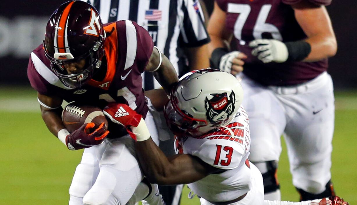 Virginia Tech's Tré Turner is tackled by North Carolina State's Tyler Baker-Williams (13) during an NCAA college football game Saturday, Sept. 26, 2020, in Blacksburg, Va. (Matt Gentry/The Roanoke Times via AP, Pool)