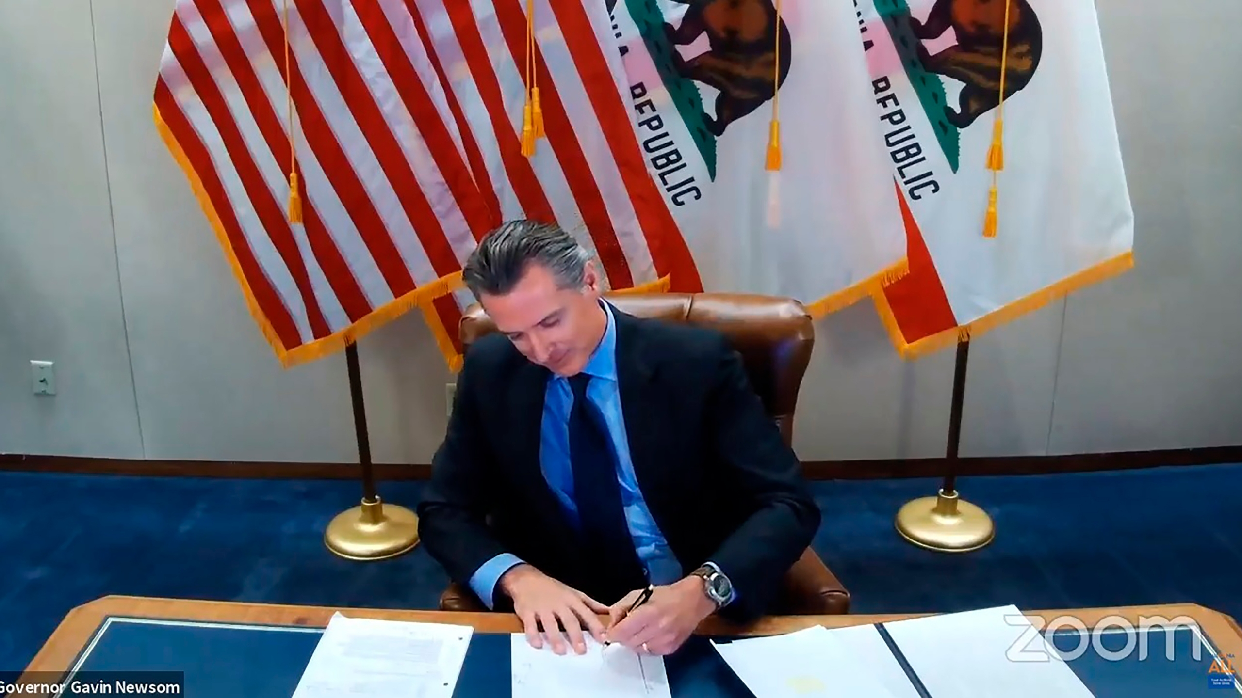 This image made from video from the Office of the Governor shows California Gov. Gavin Newsom signing into law a bill that establishes a task force to come up with recommendations on how to give reparations to Black Americans on Wednesday, Sept. 30, 2020, in Sacramento, Calif. The law establishes a nine-member task force to come up with a plan for how the state could give reparations to Black Americans, what form those reparations might take and who would be eligible to receive them. (Office of the Governor via AP)