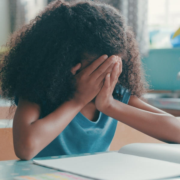 Shot of a young girl looking frustrated while doing her schoolwork in class (Getty Images)