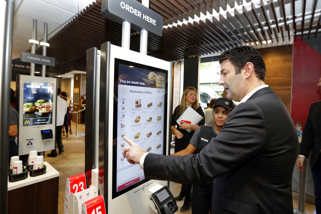 """FILE - In this Thursday, Nov. 17, 2016, file photo, McDonald's CEO Steve Easterbrook demonstrates an order kiosk, with cashier Esmirna DeLeon, during a presentation at a McDonald's restaurant in New York's Tribeca neighborhood. McDonald's has started testing mobile order-and-pay after acknowledging the ordering process in its restaurants can be """"stressful."""" The company is testing the option in California and Washington ahead of a national launch in the U.S. toward the end of 2017. Easterbrook has noted the initial stages of visiting can be """"stressful"""" and that the company is making changes to improve the overall customer experience. That includes the introduction of ordering kiosks, which executives say can help ease lines at the counter and improve order accuracy. (AP Photo/Richard Drew, File)"""