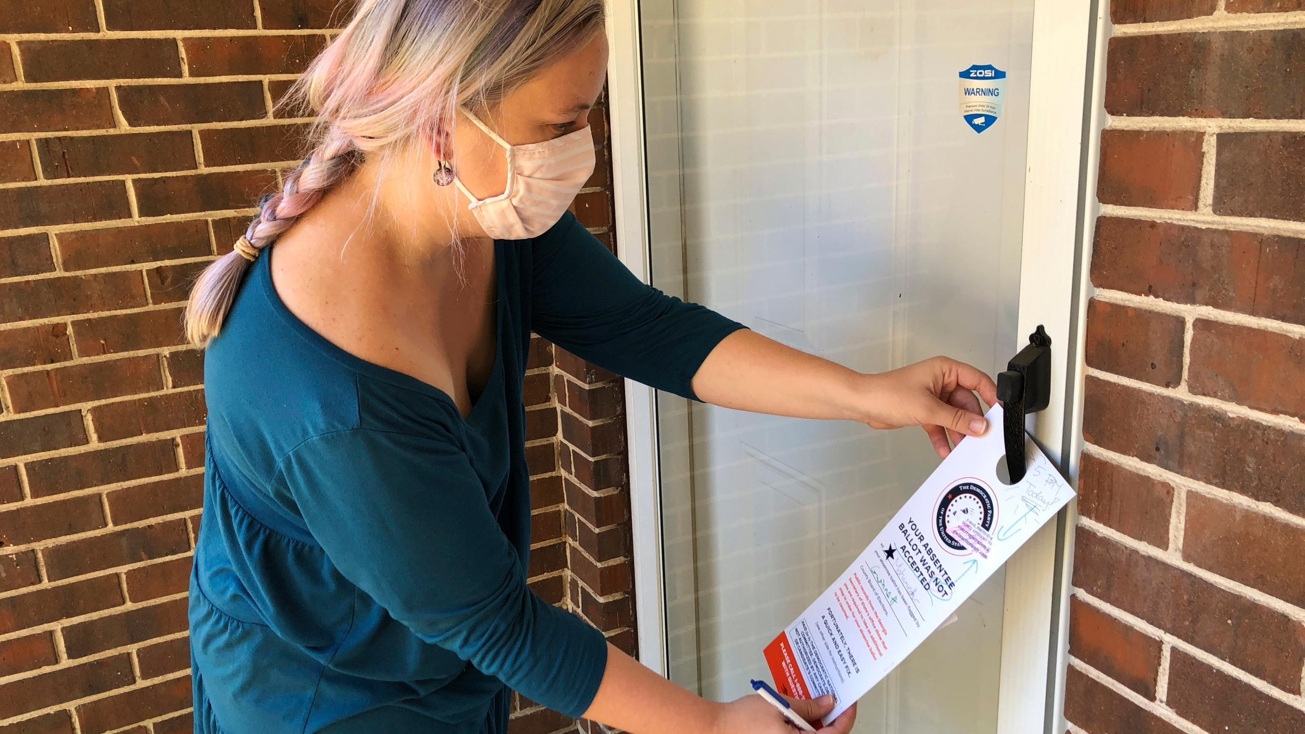 Christin Clatterbuck leaves an affidavit and information about fixing absentee ballots on the door of a home in Stone Mountain, Ga., Friday, Nov. 6, 2020. (AP Photo/Sudhin Thanawala)