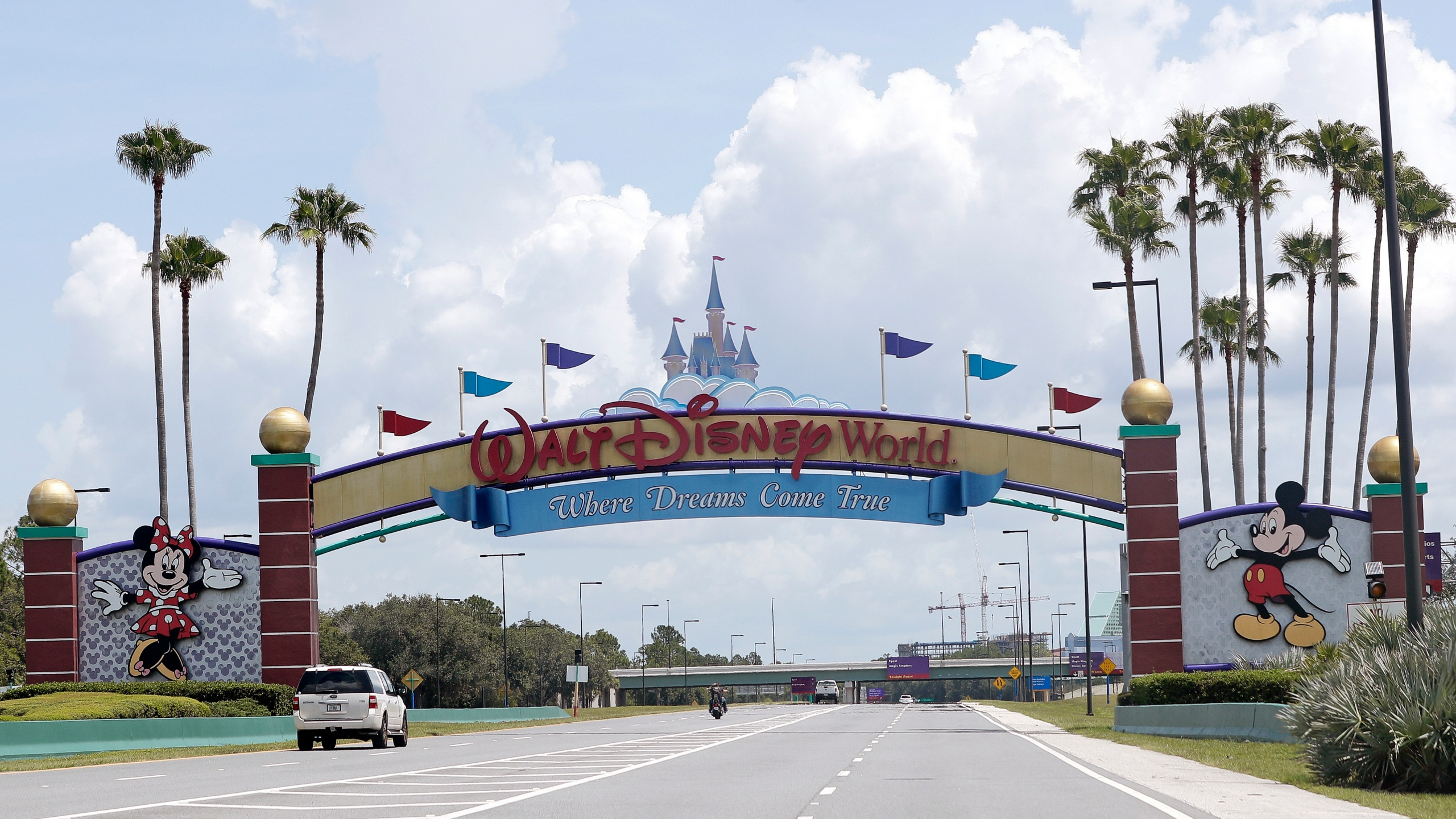 FILE - In this Thursday, July 2, 2020, file photo, cars drive under a sign greeting visitors near the entrance to Walt Disney World, in Lake Buena Vista, Fla. The Walt Disney Co. is announcing plans to lay off 4,000 more workers in its theme parks division in California and Florida due to the COVID-19 pandemic's effect on the industry. The company has been limiting attendance at its parks and changing protocols to allow for social distancing. (AP Photo/John Raoux, File)