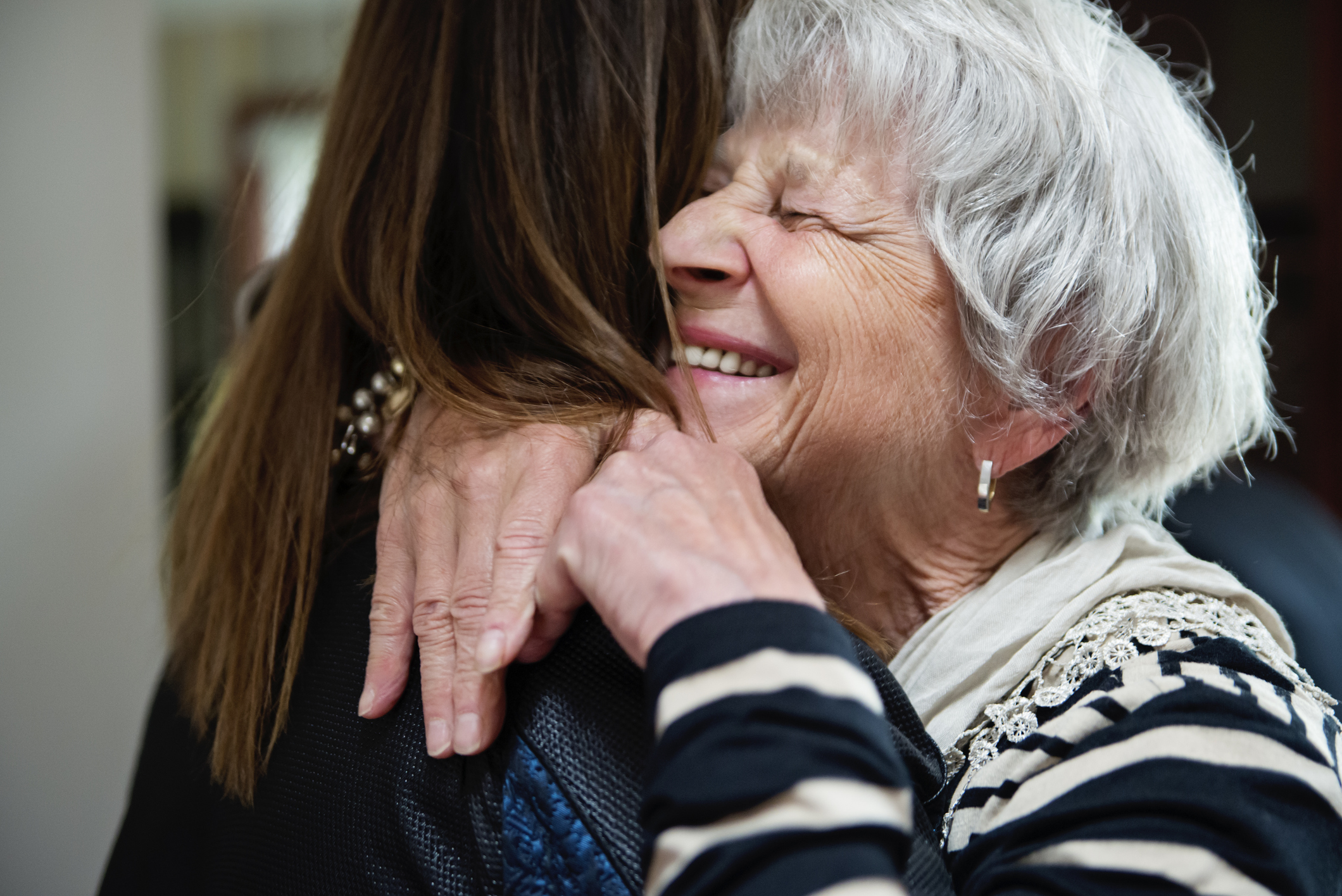 Senior grandmother and adult granddaughter hugging (Getty Images)