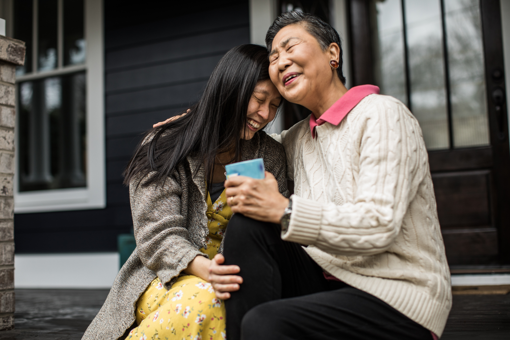 Adult woman and senior mother talking on front porch (Getty Images)