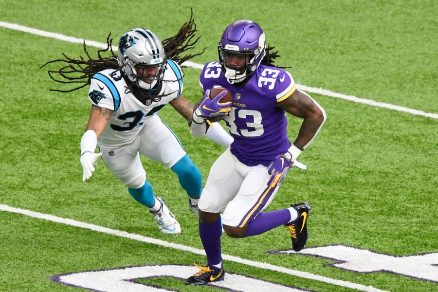MINNEAPOLIS, MINNESOTA - NOVEMBER 29: Dalvin Cook #33 of the Minnesota Vikings runs with the ball against Tre Boston #33 of the Carolina Panthers during the first half at U.S. Bank Stadium on November 29, 2020 in Minneapolis, Minnesota. (Photo by Hannah Foslien/Getty Images)