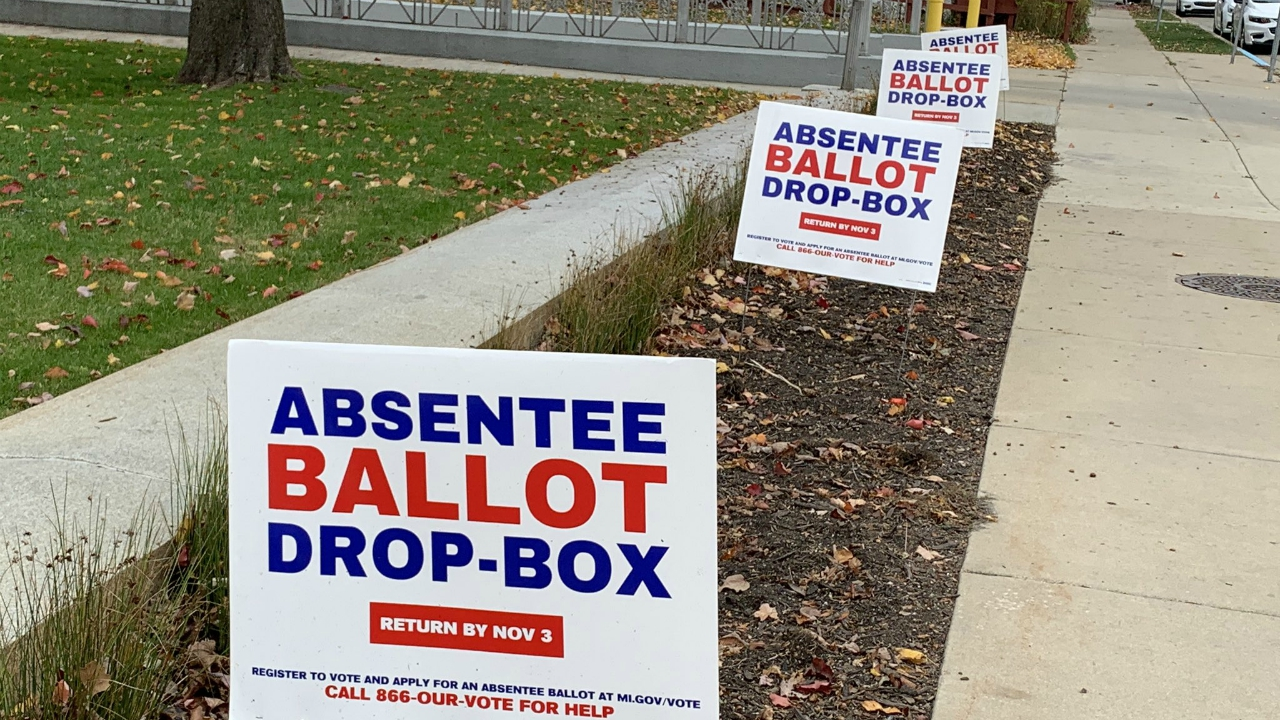 Signs direct people to an absentee ballot drop box