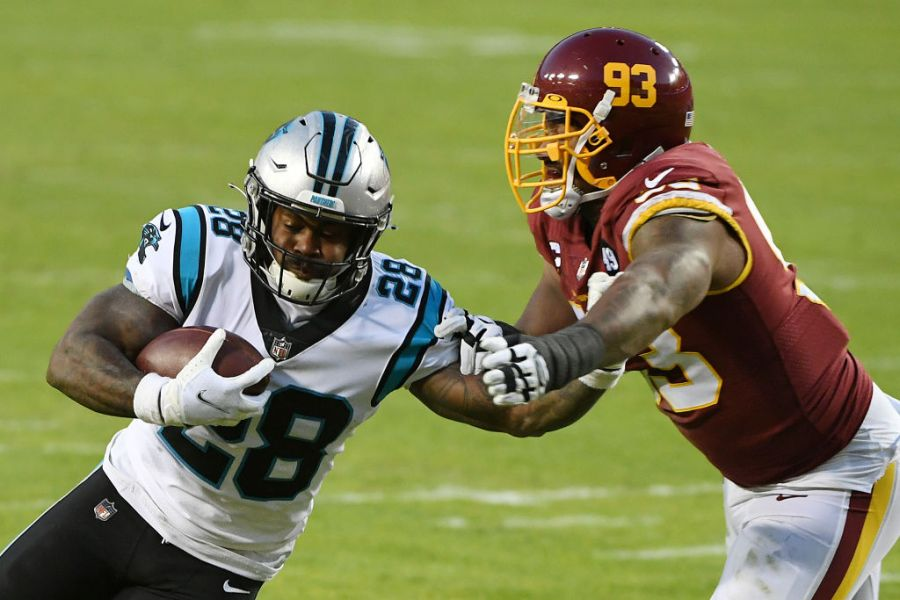 LANDOVER, MARYLAND - DECEMBER 27: Mike Davis #28 of the Carolina Panthers stiff arms Jonathan Allen #93 of the Washington Football Team at FedExField on December 27, 2020 in Landover, Maryland. (Photo by Will Newton/Getty Images)