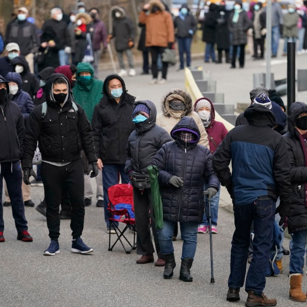 People wait in line for the COVID-19 vaccine in Paterson, N.J., Thursday, Jan. 21, 2021. The first people arrived around 2:30 a.m. for the chance to be vaccinated at one of the few sites that does not require an appointment. With millions of Americans waiting for their chance to get the coronavirus vaccine, a fortunate few are getting bumped to the front of the line as clinics scramble to get rid of extra, perishable doses at the end of the day. (AP Photo/Seth Wenig)