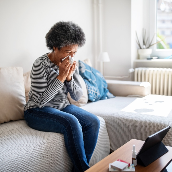 Sick woman wiping her nose with tissue paper and video conferencing with doctor using digital tablet at home during corona virus lockdown. Mature woman feeling sick and talking to her doctor online using her tablet computer at home (Getty Images)