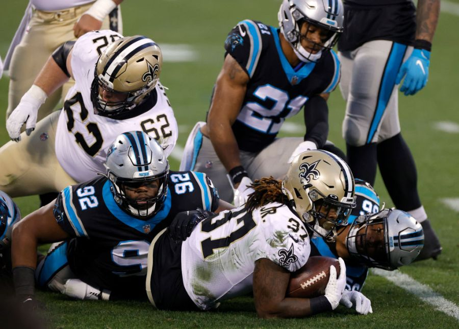 CHARLOTTE, NORTH CAROLINA - JANUARY 03: Running back Tony Jones Jr. #37 of the New Orleans Saints is tackled by defensive tackle Zach Kerr #92 and linebacker Jermaine Carter #56 of the Carolina Panthers during the first quarter of their game at Bank of America Stadium on January 03, 2021 in Charlotte, North Carolina. (Photo by Jared C. Tilton/Getty Images)