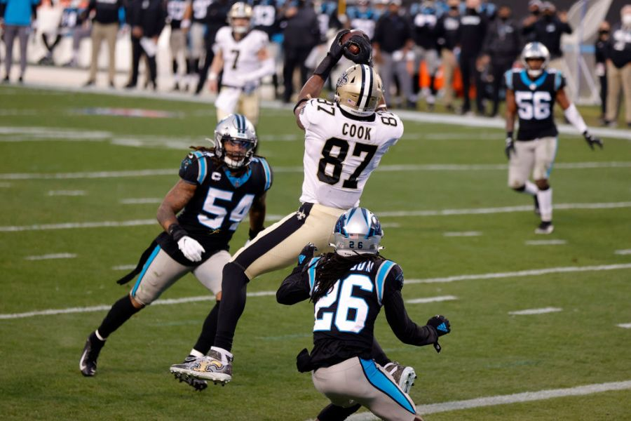 CHARLOTTE, NORTH CAROLINA - JANUARY 03: Tight end Jared Cook #87 of the New Orleans Saints catches a touchdown pass against cornerback Donte Jackson #26 and linebacker Shaq Thompson #54 of the Carolina Panthers during the first quarter of their game at Bank of America Stadium on January 03, 2021 in Charlotte, North Carolina. (Photo by Jared C. Tilton/Getty Images)