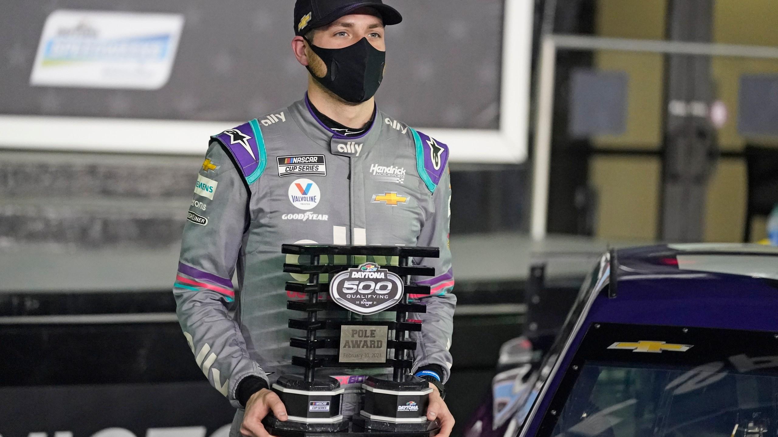 Alex Bowman holds the Pole Award Trophy in Victory Lane after winning the pole for the NASCAR Daytona 500 auto race at Daytona International Speedway, Wednesday, Feb. 10, 2021, in Daytona Beach, Fla. (AP Photo/John Raoux)