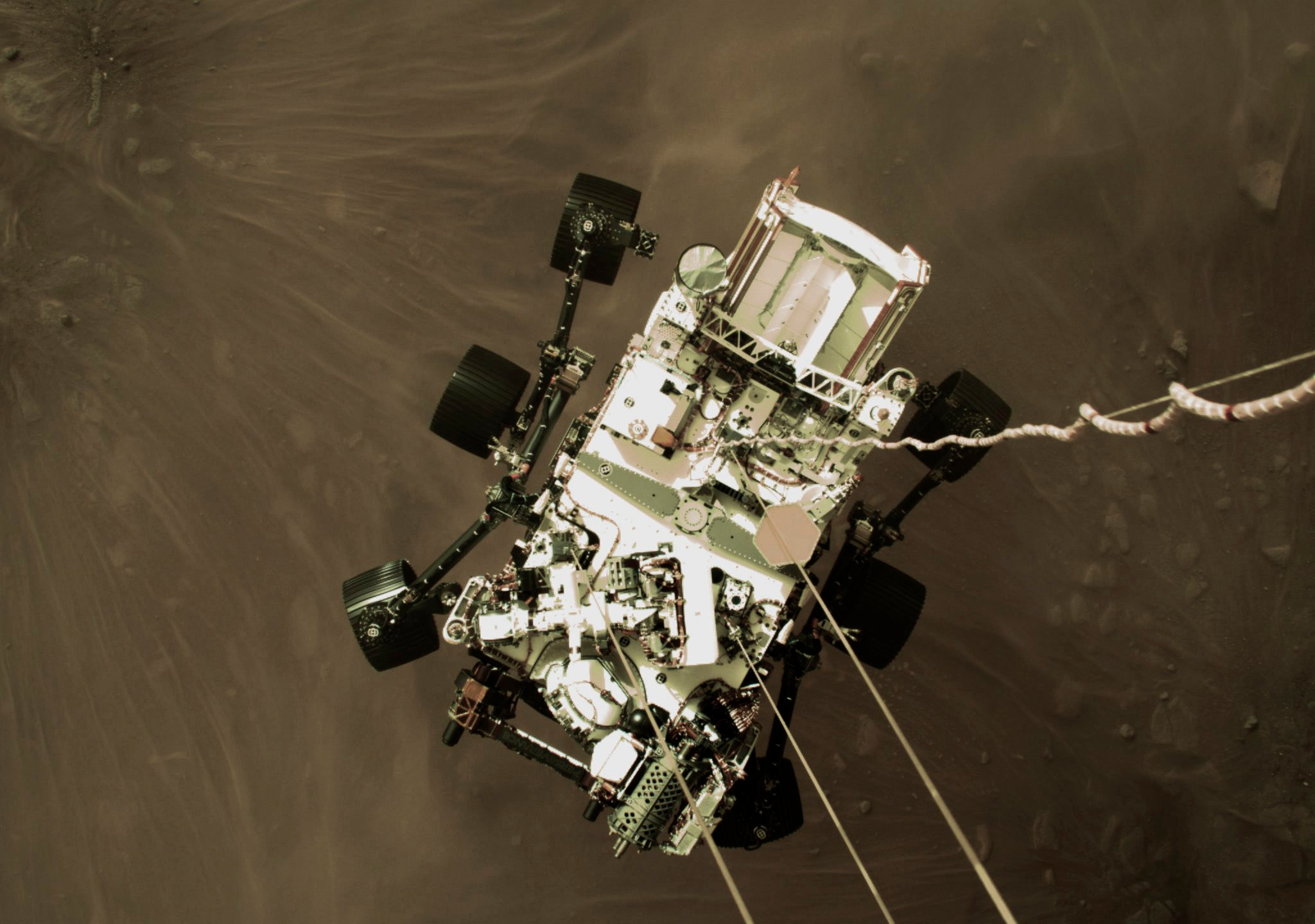 This Thursday, Feb. 18, 2021 photo provided by NASA shows the Perseverance rover lowered towards the surface of Mars during its powered descent. (NASA via AP)