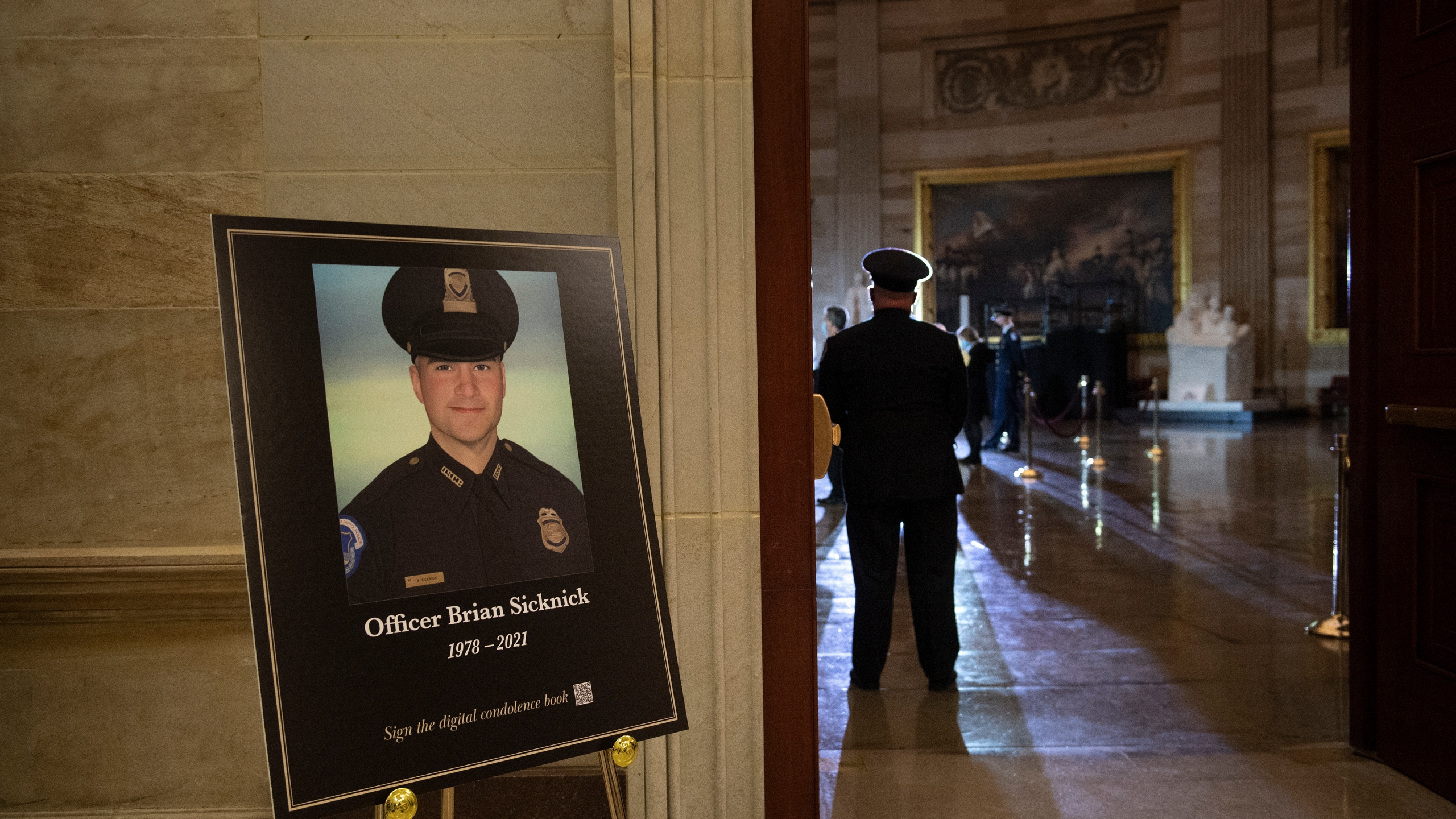 FILE - In this Feb. 2, 2021, file photo a placard is displayed with an image of the late U.S. Capitol Police officer Brian Sicknick on it as people wait for an urn with his cremated remains to be carried into the U.S. Capitol to lie in honor in the Capitol Rotunda in Washington. Federal investigators probing the death Sicknick, a U.S. Capitol Police officer killed in the Jan. 6 riot, have zeroed in on a suspect seen on video appearing to spray a chemical substance on the officer before he later collapsed and died, two people familiar with the matter told The Associated Press. (Brendan Smialowski/Pool via AP, File)
