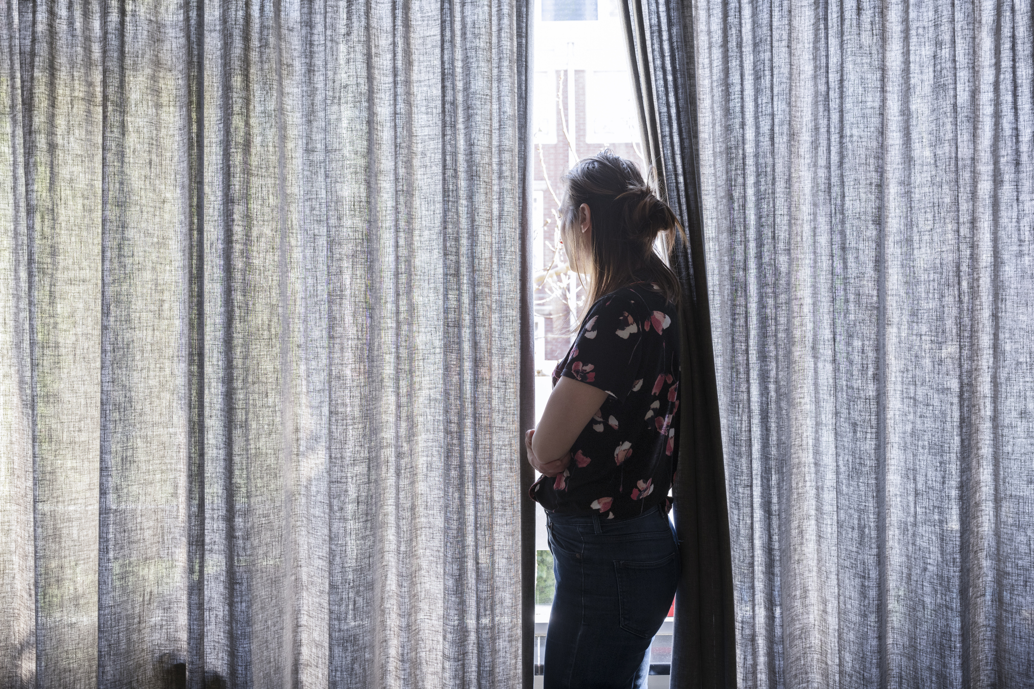 Woman looking out window (Getty Images)