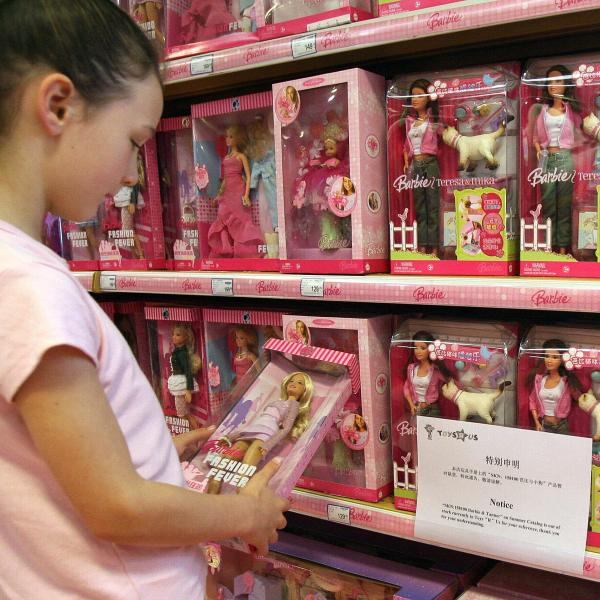 "A young girl holds a Barbie doll next to a notice saying that the toy ""Barbie and Tanner"" made by US toy giant Mattel, which has just been recalled in the US, is out of stock at a Toys ""R"" Us store in Shanghai, 15 August 2007. The US Consumer Product Safety Commission announced the recall of millions of toys manufactured by Mattel Inc., including the Barbie and Tanner play sets, at the commission's headquarters in Bethesda, Maryland. According to the commission, the play sets' ""scooper"" accessory has a small magnet that can come loose and if more than one magnet is swallowed they can attract each other and cause intestinal perforation or blockage, which can be fatal. AFP PHOTO/Mark RALSTON (Photo credit should read MARK RALSTON/AFP via Getty Images)"